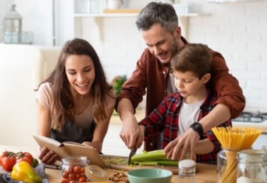 Genitori insegnano al figlio come tagliare le verdure.